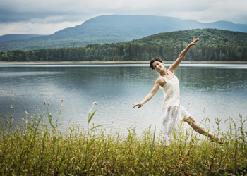 Woman wearing a white dress is dancing on a field in front of a lake in the mountails
