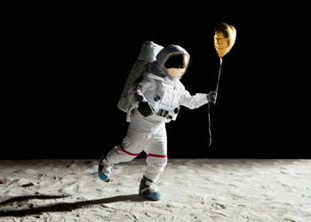 Astronaut walking on the moon holding a gold balloon