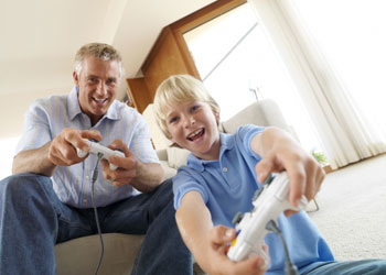 Father and son having fun while playing videogames in the livingroom