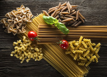 Different types of wholemeal and classic Pasta with tomatos and basil on dark wood