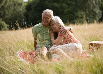 Married senior citizens having a picknick in nature on a big field in summer