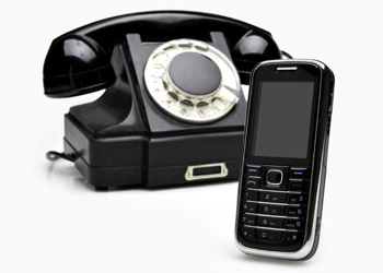 Image of an old black telephone and a black cell phone
