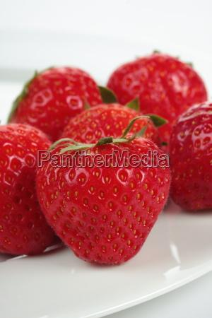 eine menge erdbeeren auf einen teller