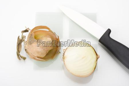 halbierte zwiebel und ein messer auf