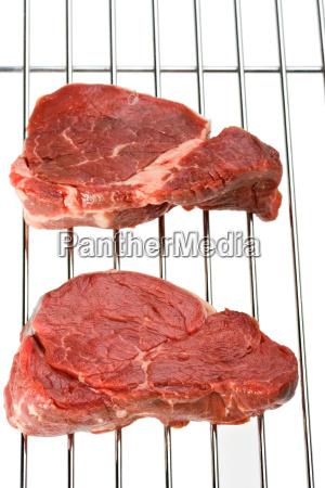 rohe steak auf einem grillrost isoliert