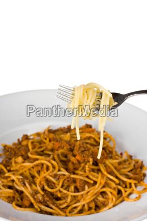 gabel ueber einen teller mit spaghetti