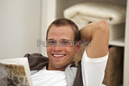 laechelnder jungen mann liest ein buch
