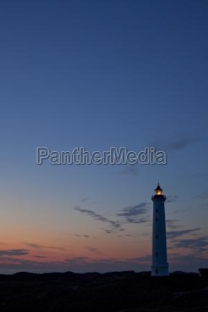 silhouette eines daenischen leuchtturms bei sonnenuntergang