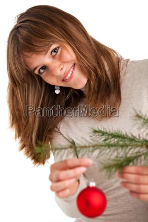 huebsche junge frau schmueckt einen weihnachtsbaum