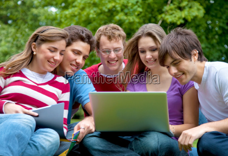 friends with laptop outdoors