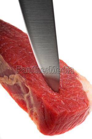 kuechenmesser schneidet durch ein rohes steak
