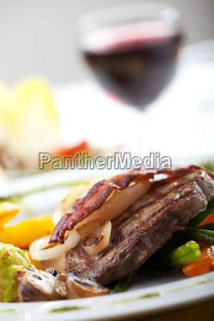 speckscheibe auf einem steak mit gemuese