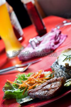 schweinesteak und zucchini mit salat im