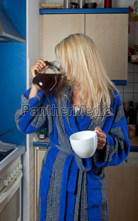 schlaefrige blonde frau trinkt kaffee aus