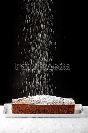 puderzucker faellt auf einen schokoladenkuchen