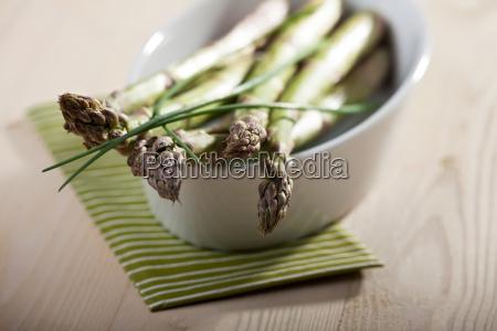 roher gruener spargel und schnittlauch