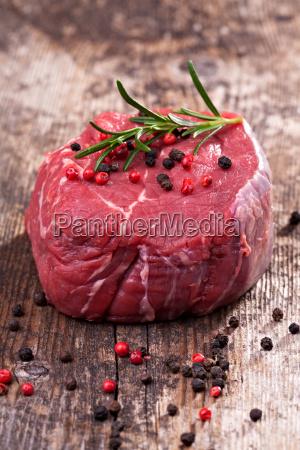 rohen steak mit pfeffer auf holz