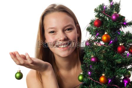 frau schmueckt einen weihnachtsbaum