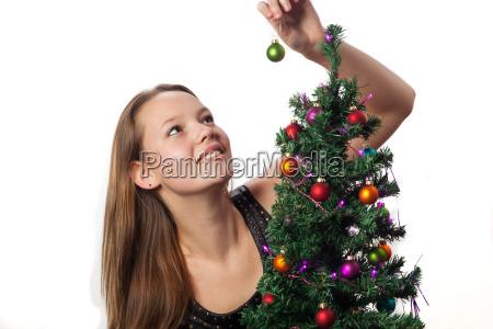 frau schmueckt einen christbaum