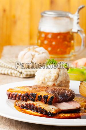 bayerischer schweinebraten auf teller mit semmelknoedel