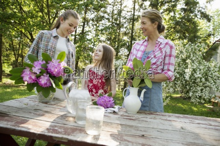 three people gathering flowers and arranging