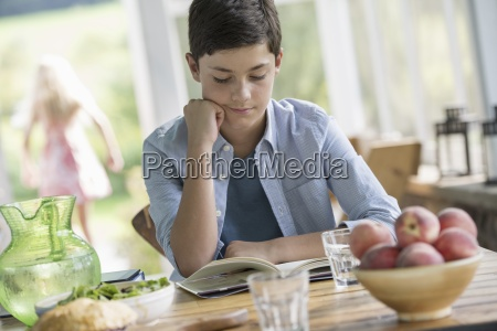 a young boy sitting reading a