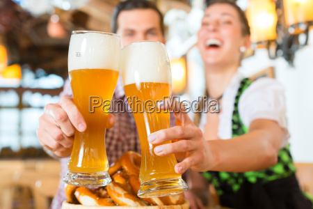 bavarian couple clinking beer