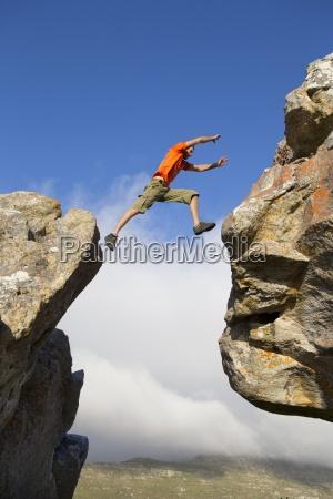 male rock climber jumping between rocks