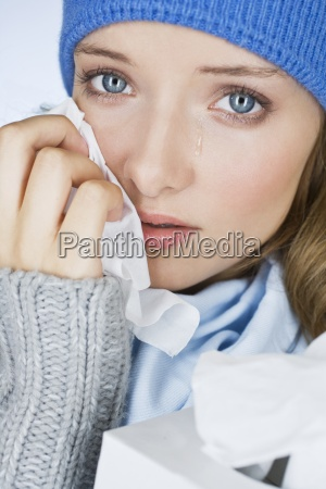 a young woman crying wiping her