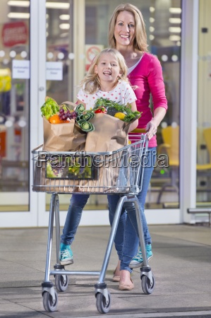 mother pushing daughter in trolley outside