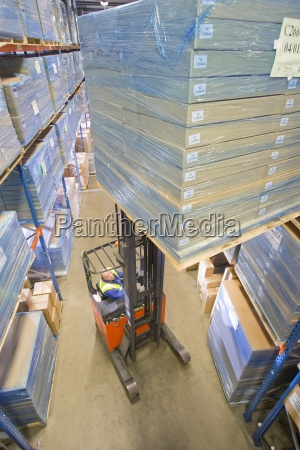 warehouse worker moving boxes on forklift