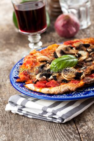 champignon pizza auf einem holztisch