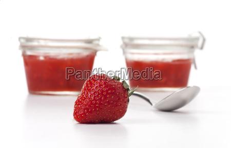 erdbeere loeffel und marmelade auf weiss