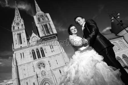 newlyweds posing in front of cathedral