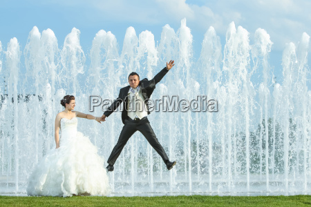groom jumping in front of water