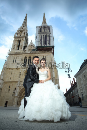 newlyweds holding hands in city
