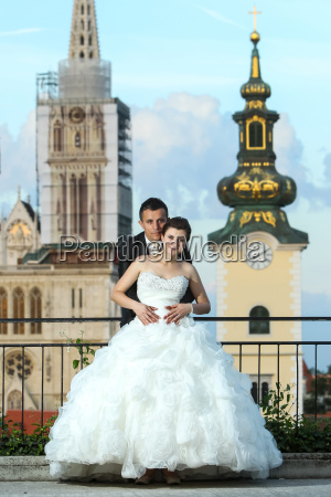 bride and groom posing in city