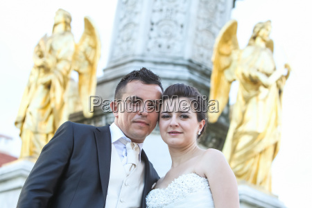 newlyweds posing in front of fountain