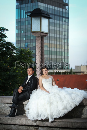 newlyweds sitting next to street lamp