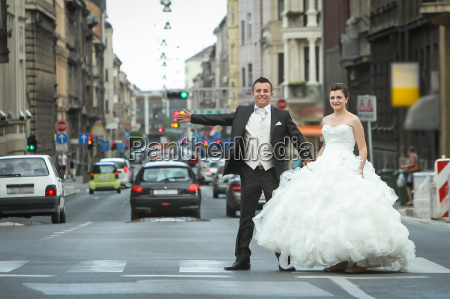 newlyweds standing on pedestrian crossing