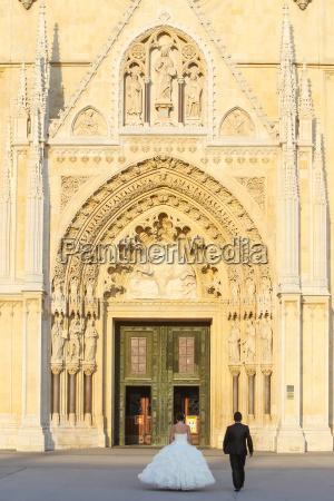 newlyweds walking toward cathedral