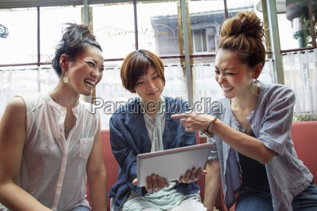 three women looking at a digital