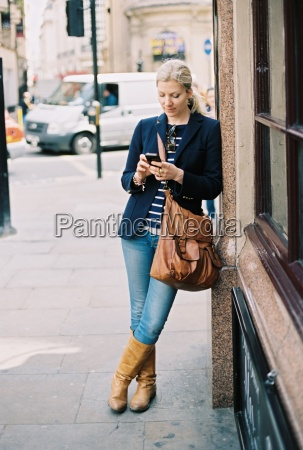 a woman checking her phone leaning