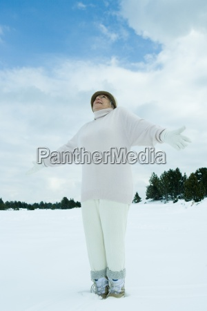 senior woman standing on snow arms