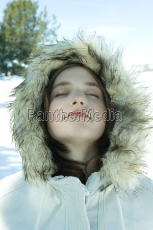 teen girl wearing parka in snow