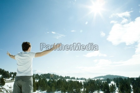 young man standing facing snowy mountain
