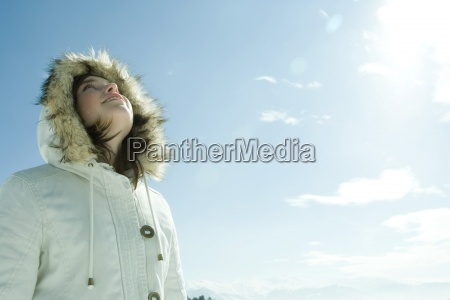 teen girl wearing parka looking up