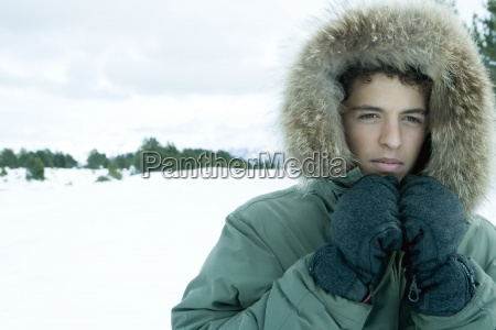 teen boy wearing parka in snowy