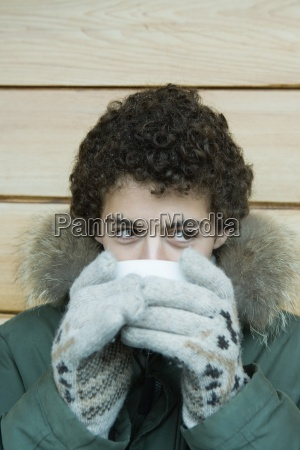 teen boy in winter clothes drinking