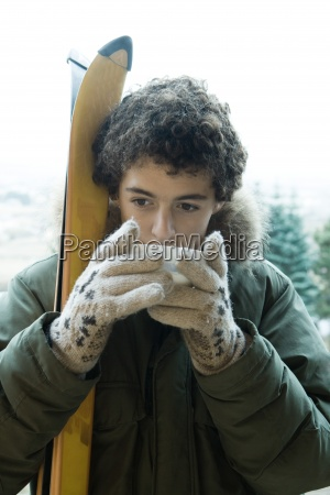 teen boy with skis drinking warm
